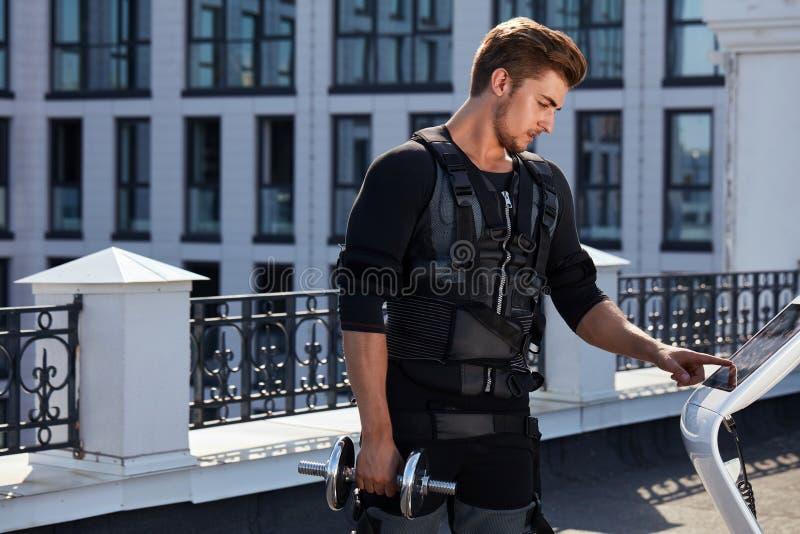 Sporty silny facet trzyma macanie i dumbbell ekran ems przyrząd zdjęcie royalty free