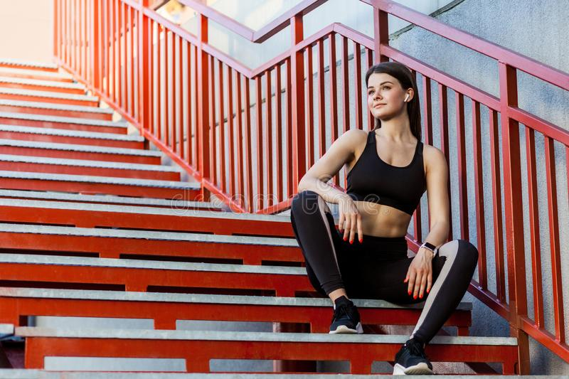 Sporty slim happy young beautiful woman in black fashionable sportwear sitting on the red stairs and relaxing during outdoor. Exercises workout. Outdoor, sport stock image