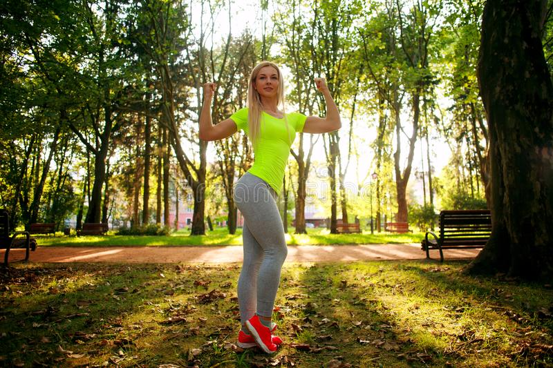 Sporty slim woman pose in green summer city park royalty free stock images