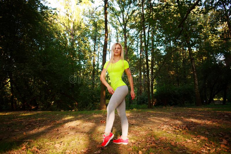 Sporty slim woman pose in green summer city park stock photography