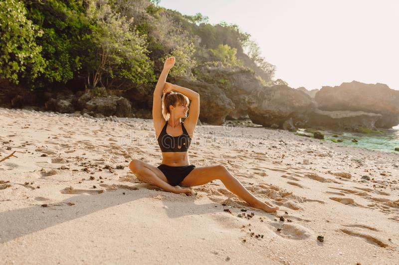 Sporty slim woman practice yoga at beach with sunset light stock images