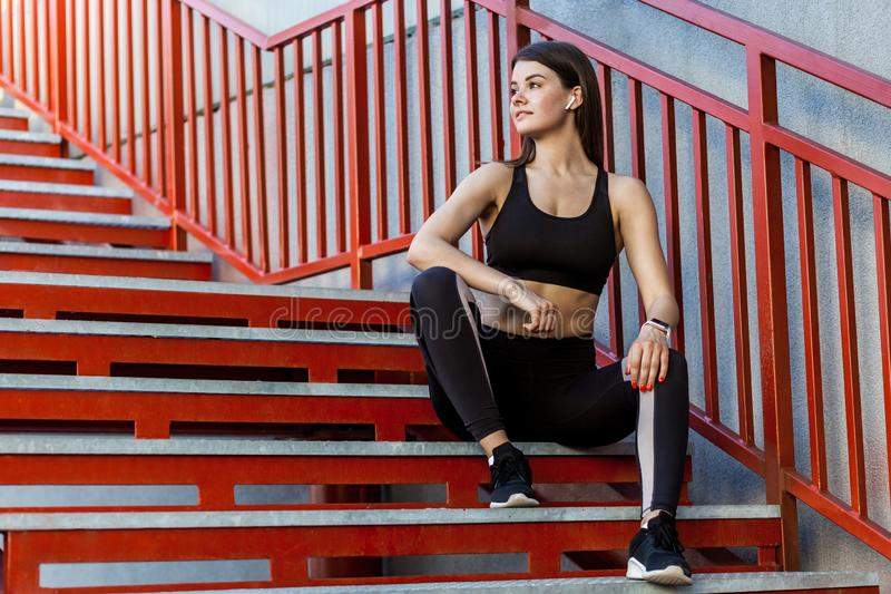 Sporty slim young beautiful woman in black fashionable sportwear sitting on the red stairs and relaxing during outdoor exercises royalty free stock photography