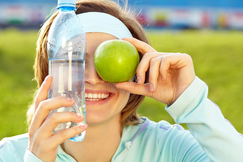 Sporty smiling woman with a water bottle and green apple royalty free stock photo