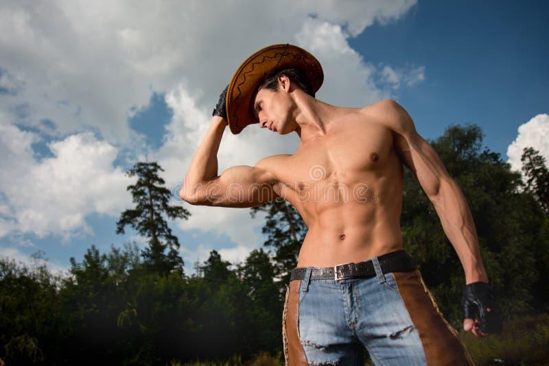 Sporty, sportowy, mięśniowy seksowny mężczyzna w kowbojskim stroju, zdjęcie stock