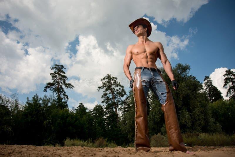 Sporty, sportowy, mięśniowy seksowny mężczyzna w kowbojskim stroju, obrazy stock
