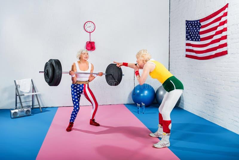 sporty starszy kobiety dmuchania gwizd i patrzeć starszego sportsmenka udźwig fotografia royalty free