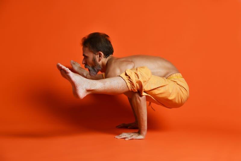 Sporty starszy mężczyzna robi ręki równowagi ćwiczeniu dla siły, joga, pilates trenuje, obraz stock