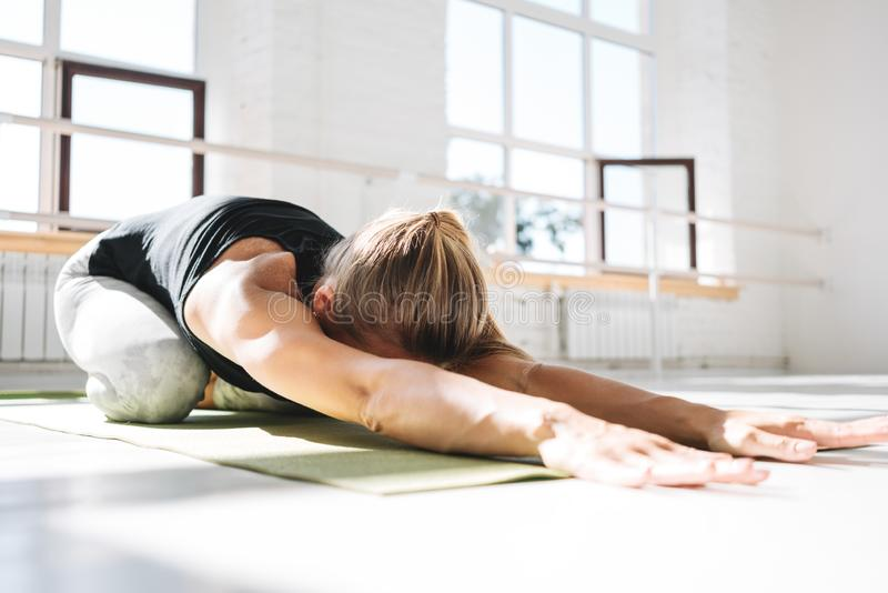 Sporty strong woman doing practicing yoga fitness mat in sunny gum royalty free stock images