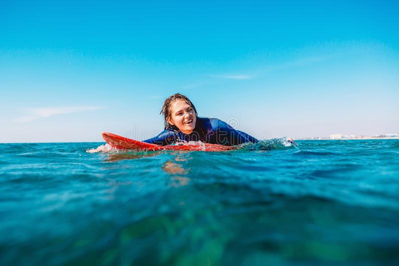 Sporty surf girl is smiling and rowing on surfboard. Woman with surfboard in ocean. royalty free stock photography