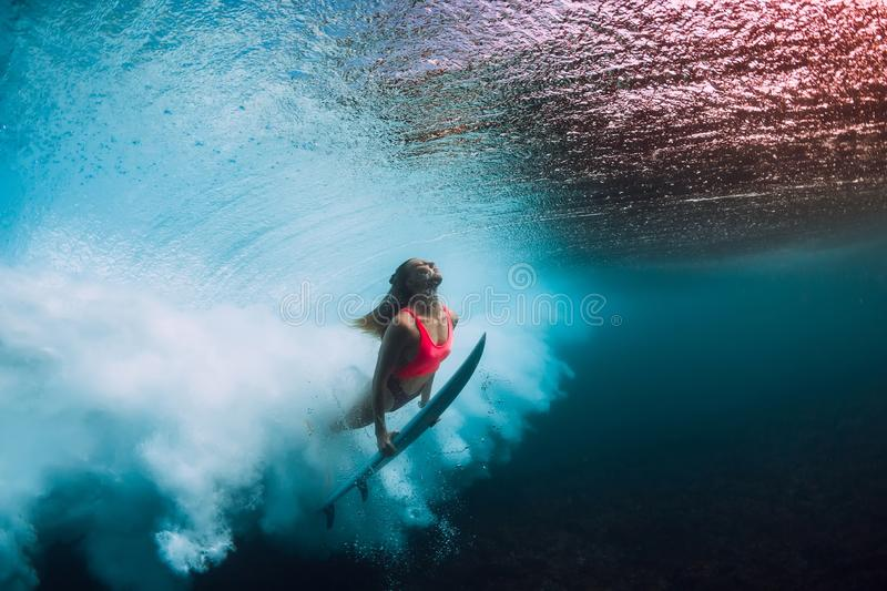 Sporty surfer woman dive underwater with under barrel wave. Sporty surfer woman dive underwater with under wave stock photo