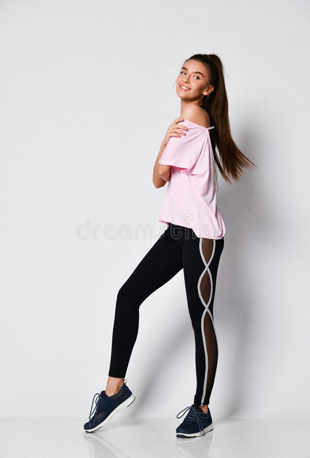 Sporty szczupła brunetki sprawności fizycznej kobieta podczas treningu ćwiczenia w purpurach bawi się odzież na szarym pełnym cie obraz royalty free