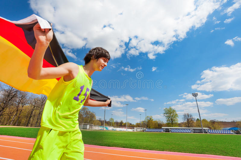 Sporty teenage boy running with flag of Germany royalty free stock images