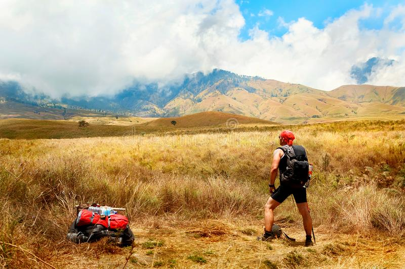 Sporty tourist guy with backpack looking at the mountains. Indonesia. Lombok Island stock photo