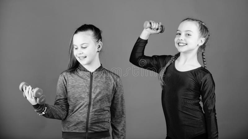 Sporty upbringing. Easy exercises with dumbbell. On way to stronger body. Girls exercising with dumbbells. Beginner. Dumbbells exercises. Children hold stock photo