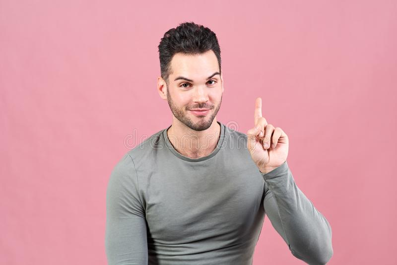 Sporty white-skinned man in a gray t-shirt raises his finger up and enthusiastically lets you know that he had a brilliant idea. Sporty white-skinned man in royalty free stock photography