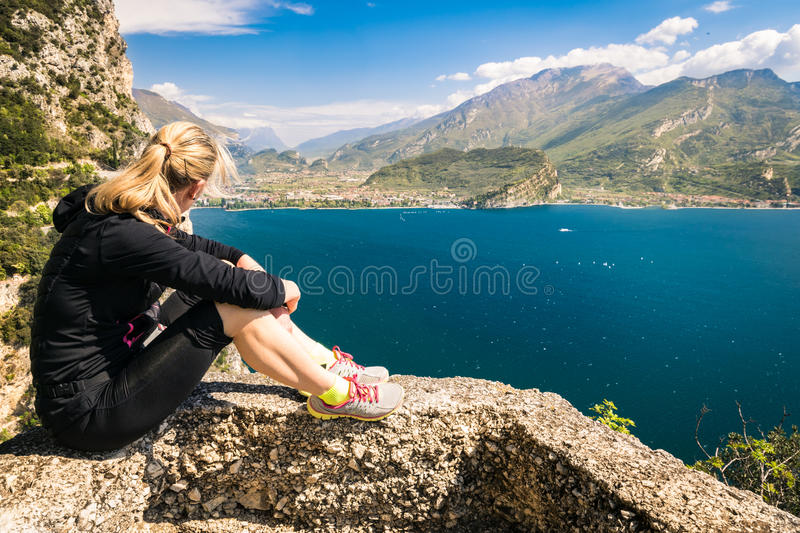 Sporty woman admire the panorama from the Ponale trail in Riva d. Young sporty woman admire the panorama from the Ponale trail in Riva del Garda, Italy royalty free stock photo