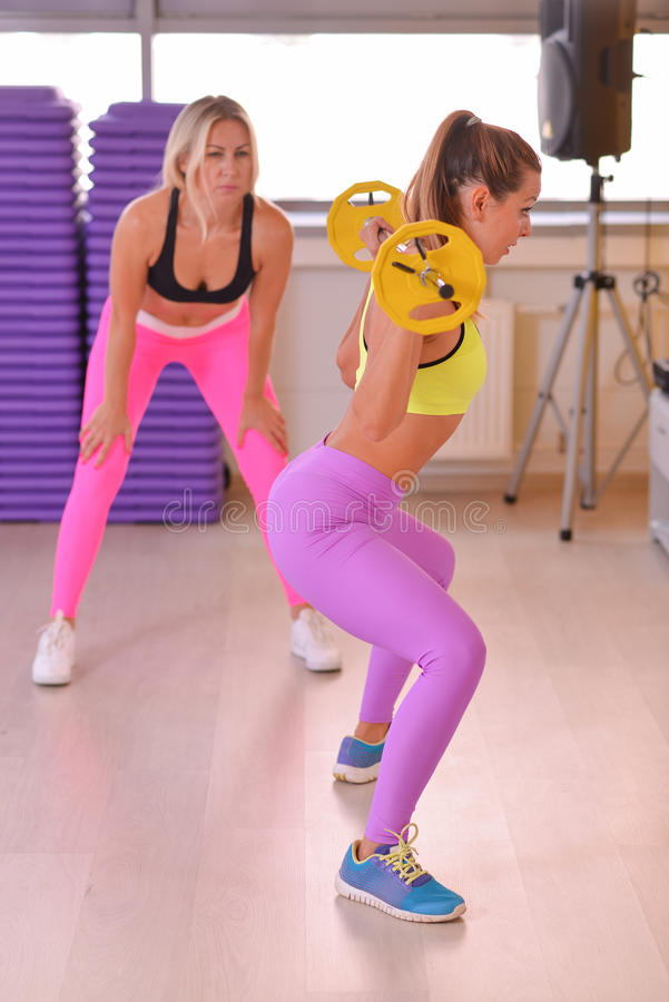 Sporty woman with barbell doing squats, instructor monitors the process stock photos