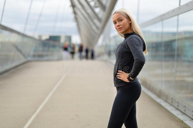 Sporty Woman in Black Workout Outfit Standing At Modern Bridge In City royalty free stock photo