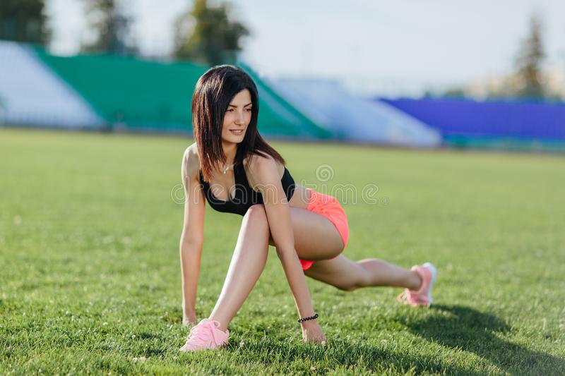 Sporty woman brunette runner in sport wear doing workout sessions on the field in a sports suit in the summer on a hot sunny day. Sporty woman brunette runner stock photos
