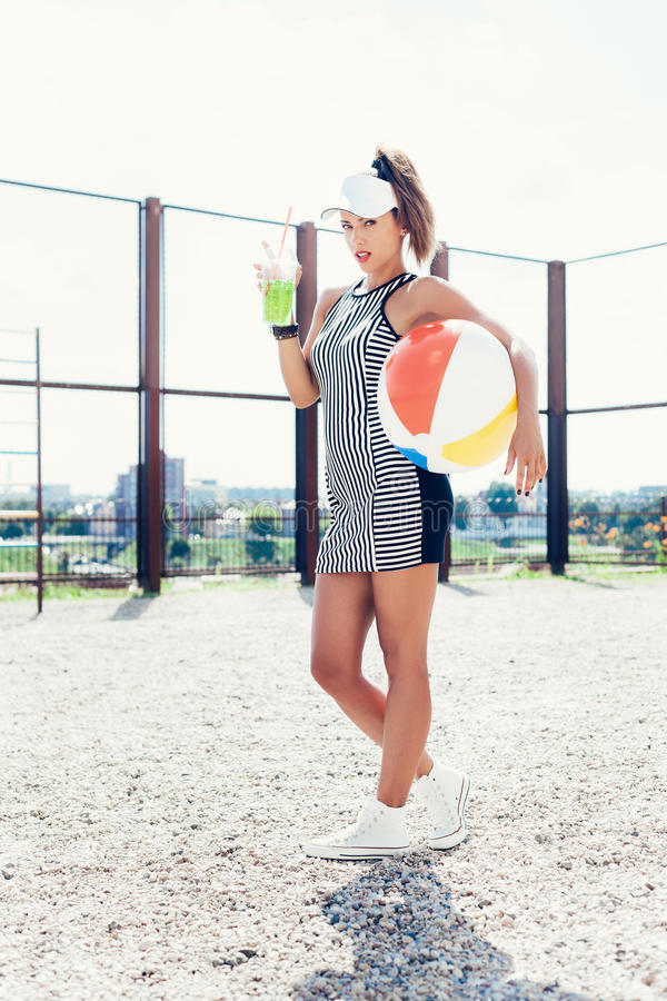 Sporty woman with color ball drinking water against the sportsground. Outdoor lifestyle portrait stock photos