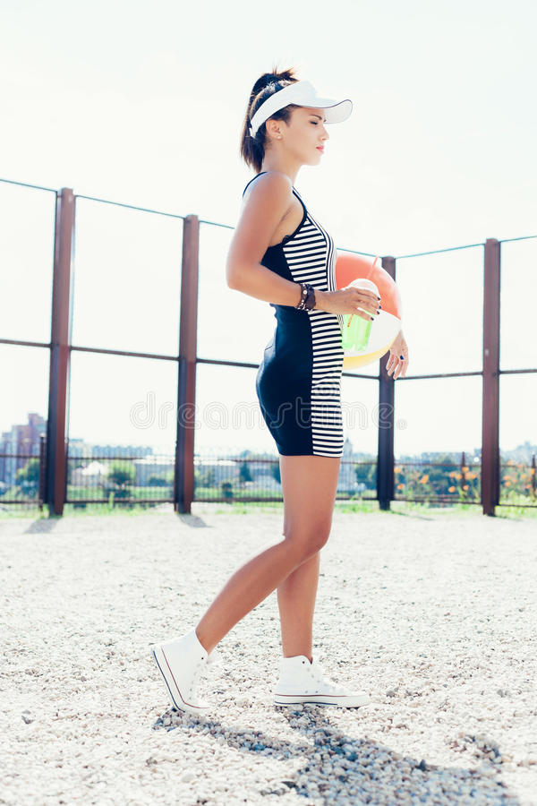Sporty woman with color ball drinking water against the sportsground. Outdoor lifestyle portrait royalty free stock images
