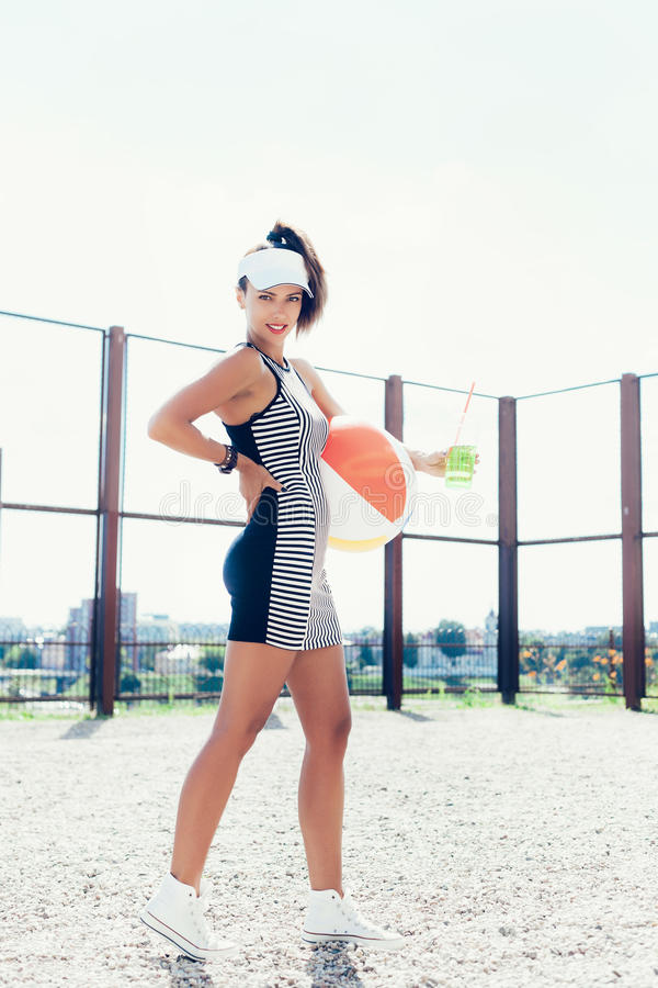 Sporty woman with color ball drinking water against the sportsground. Outdoor lifestyle portrait royalty free stock photos
