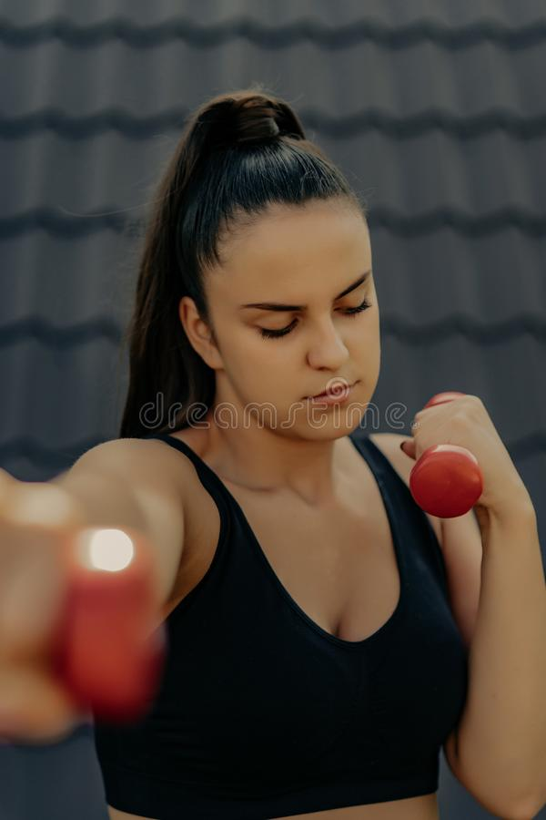 Sporty woman doing boxing exercises, making direct hit with dumbbells. Photo of muscular female wearing sportswea royalty free stock photography