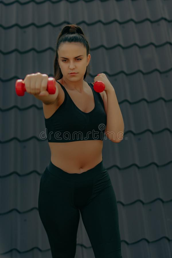 Free Sporty Woman Doing Boxing Exercises, Making Direct Hit With Dumbbells. Photo Of Muscular Female Wearing Sportswea Royalty Free Stock Image - 157566106