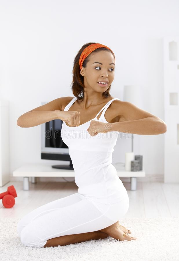 Sporty woman doing exercise. Portrait of happy sporty woman doing exercise at home stock image