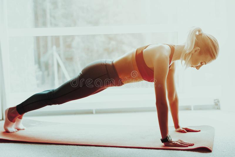 Sporty Woman Is Doing Push Ups On The Gym Carpet. Young Sporty Woman Is Doing Push Ups On The Gym Carpet. Active Lifestyle. Doing Fitness At Home. Holiday royalty free stock images