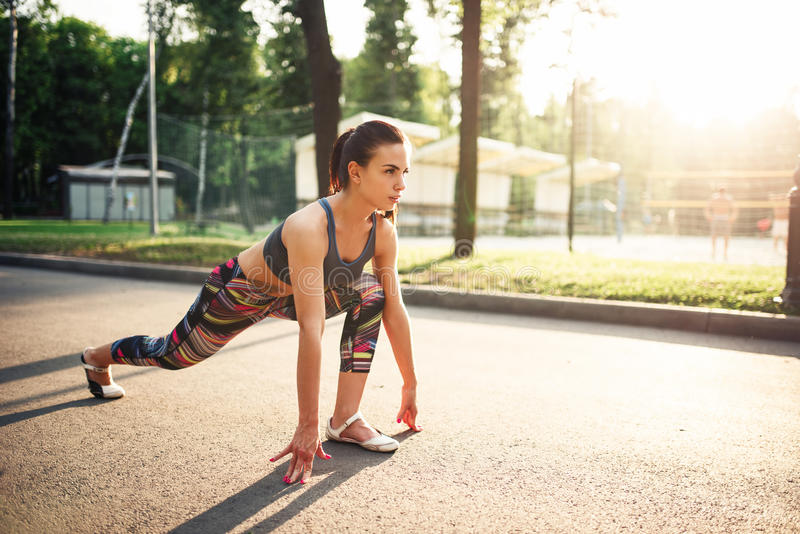 Sporty woman doing stretching exercises in park royalty free stock image