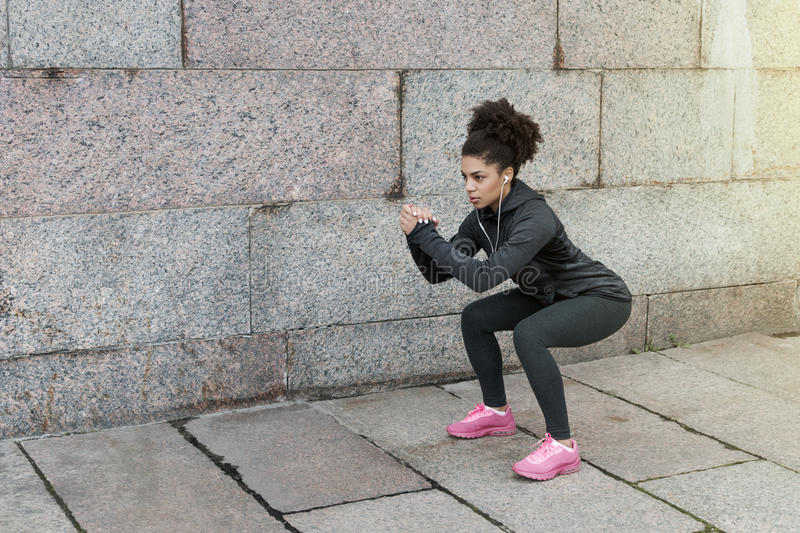 Sporty woman doing warm up squat. Stretching near a wall stock photos