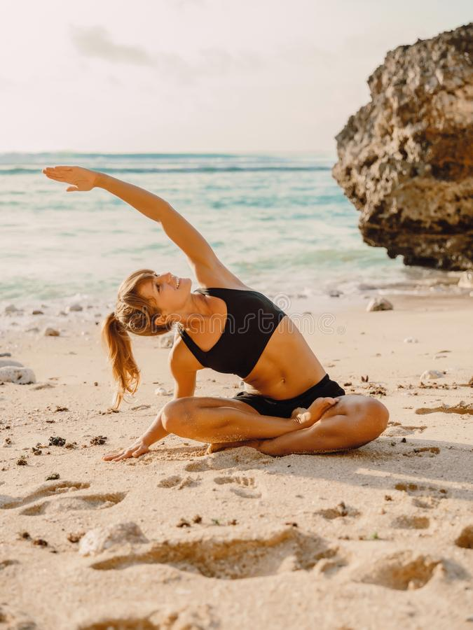 Sporty woman doing yoga at sandy beach with sunset stock photos