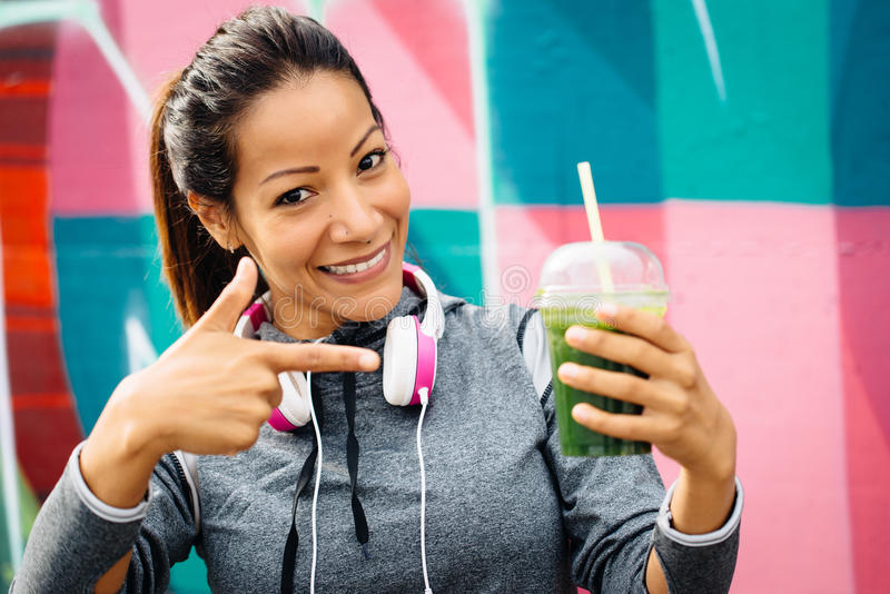Sporty woman drinking detox smoothie. Successful fitness urban woman taking a rest for drinking and recommending detox smoothie. Healthy nutrition and lifestyle royalty free stock image