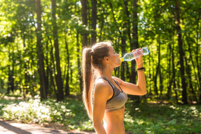Sporty woman drinking water outdoor on sunny day. Sporty woman drinking water outdoor on sunny day stock image
