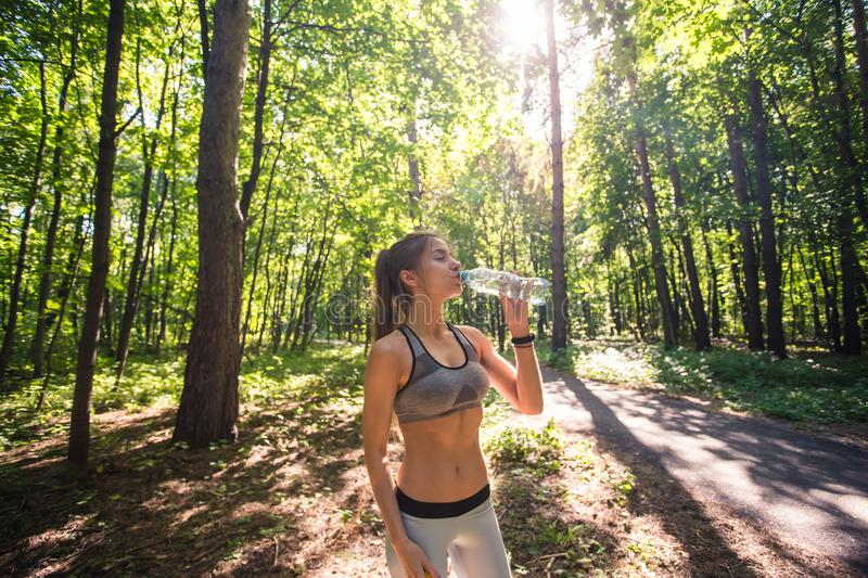 Sporty woman drinking water outdoor on sunny day. Sporty woman drinking water outdoor on sunny day royalty free stock photos