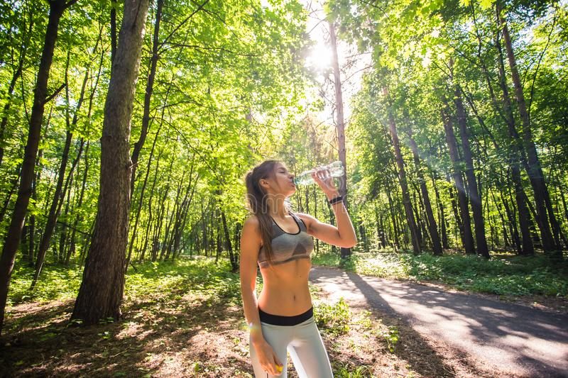 Sporty woman drinking water outdoor on sunny day. Sporty woman drinking water outdoor on sunny day stock photos
