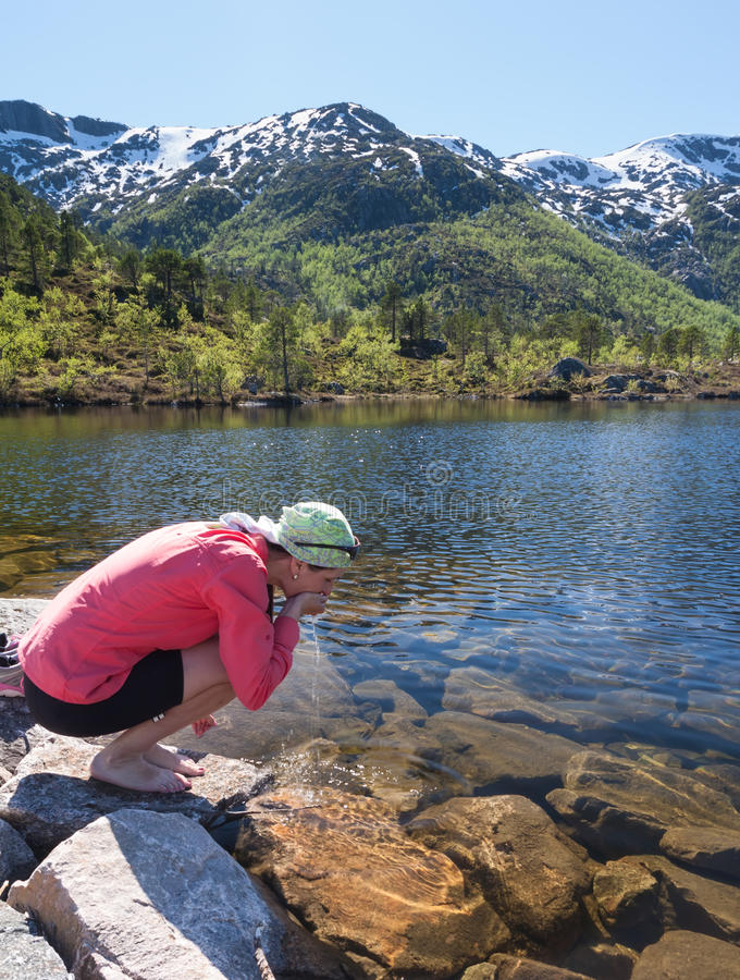 Sporty woman drinks water from clean mountain lake stock photography