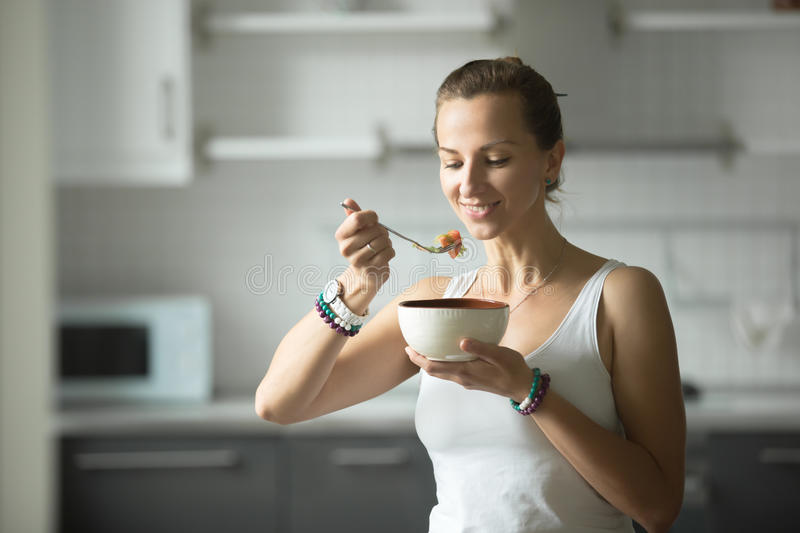 Sporty woman eating in Tree pose royalty free stock photos