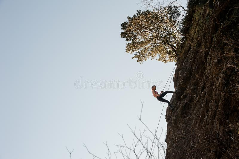 Sporty woman equipped with a rope abseiling on the sloping rock stock photos