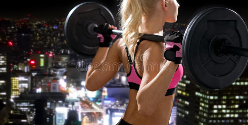 Sporty woman exercising with barbell from back. Fitness, sport and dieting concept - sporty woman exercising with barbell from back stock photography