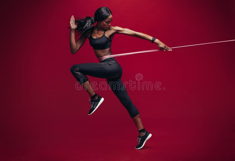 Sporty woman exercising with resistance band. On red background. African female athlete working out with elastic bands in studio stock photo
