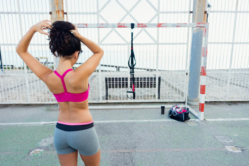 Sporty woman getting ready for fitness trx workout. Back view of sporty young woman getting ready for fitness trx workout with straps. Healthy lifestyle and stock photography