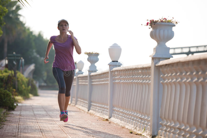 Sporty woman jogging. On sidewalk at early morning royalty free stock image