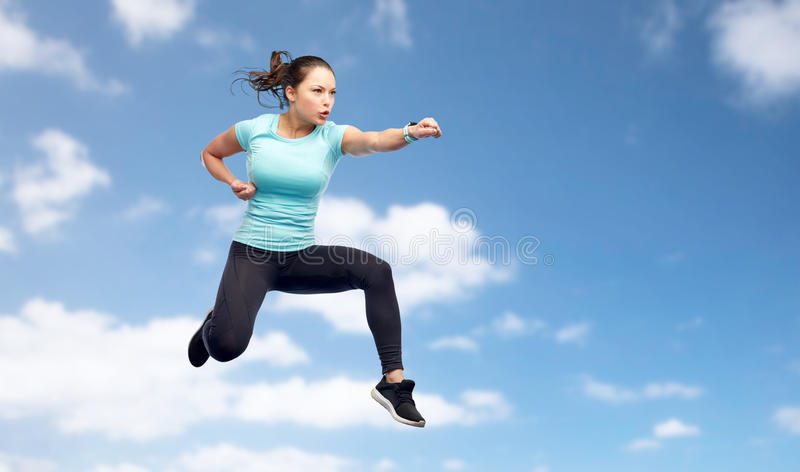 Sporty woman jumping in fighting pose over sky. Sport, fitness, motion and people concept - happy young woman jumping in air in fighting pose over blue sky royalty free stock photos