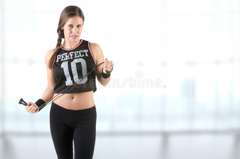 Sporty woman with a jumping rope, isolated in white. Sporty woman with a jumping rope, in a gym royalty free stock photos