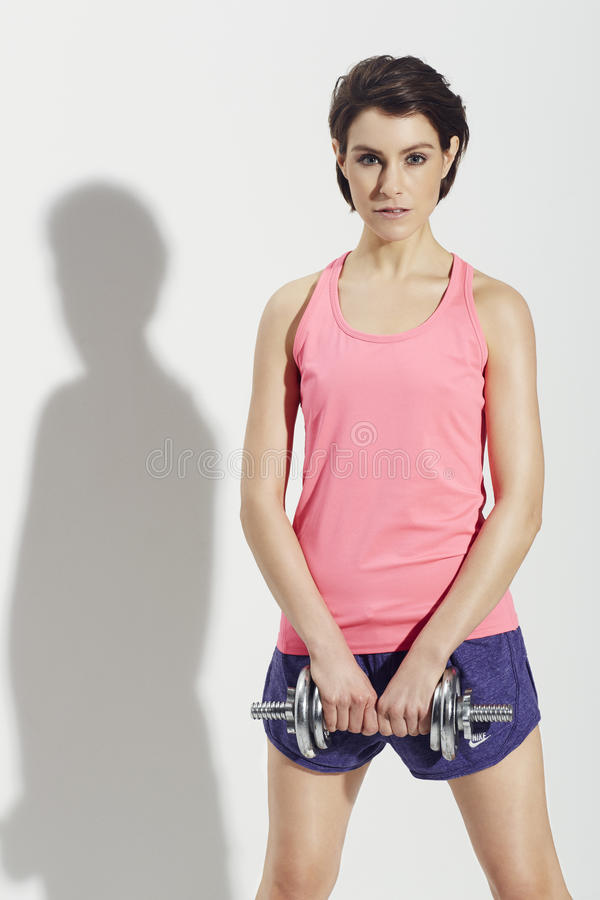 Sporty woman lifting weights royalty free stock image