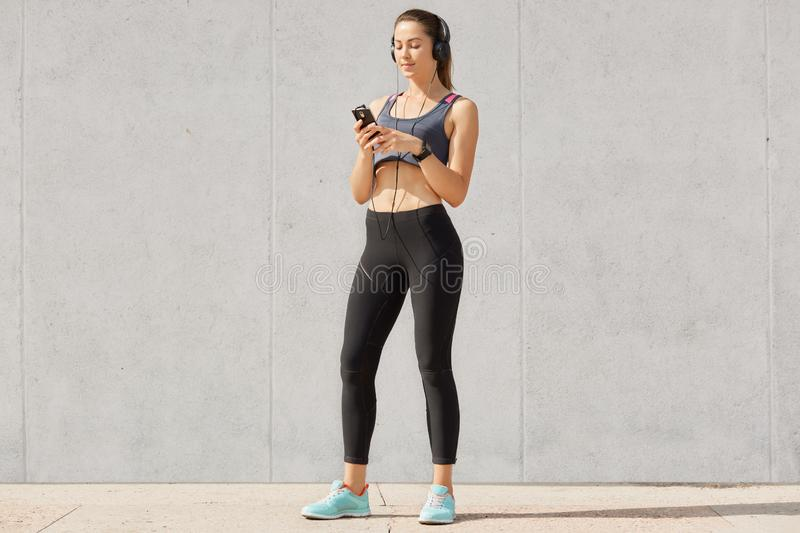 Sporty woman listening music in headphones while training in gymnasium, dressed top and leggins, shows bared stomach, posing over. Gray studio background stock photography