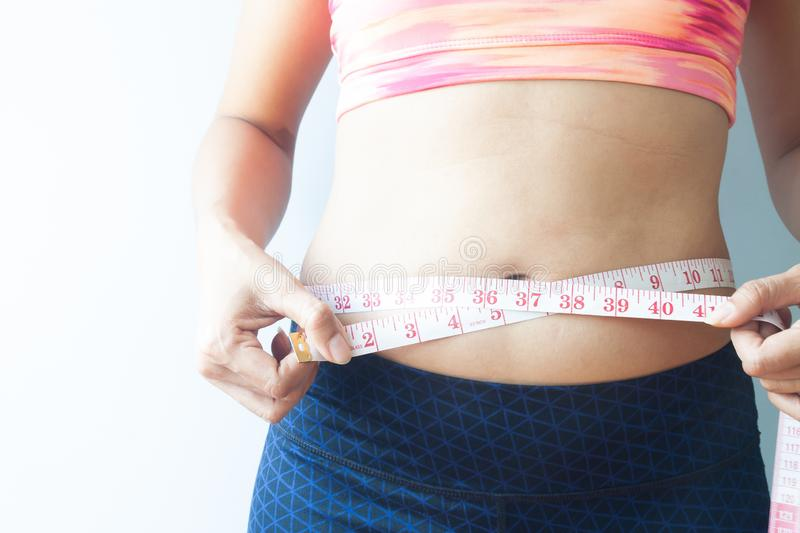 Sporty woman measuring body, get rid of belly fat. Healthy concept royalty free stock images