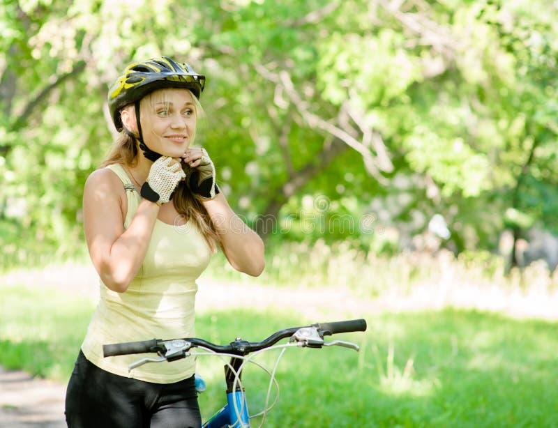 Sporty woman on mountain bike putting biking helmet stock image